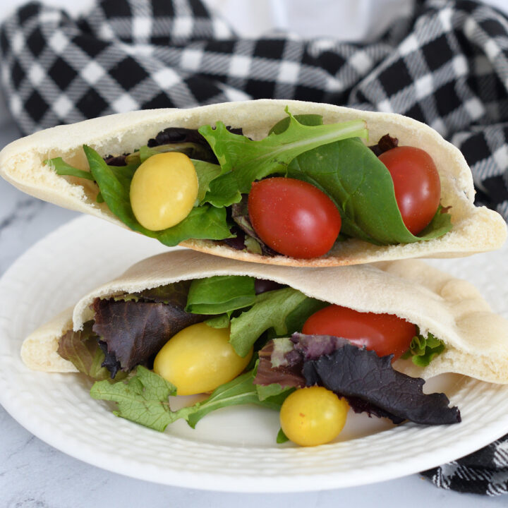 pita bread filled with lettuce and tomatoes on a plate