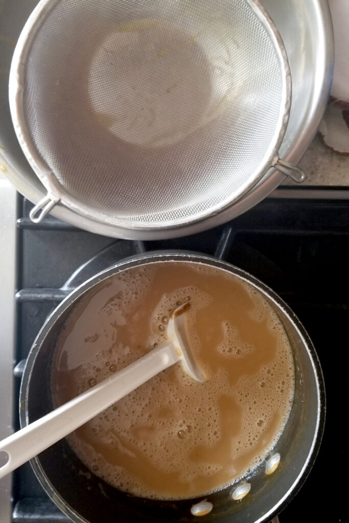 a pot of custard on a stove with a bowl and strainer nearby.