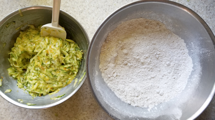 a bowl of zucchini with eggs and another bowl with flour and spices