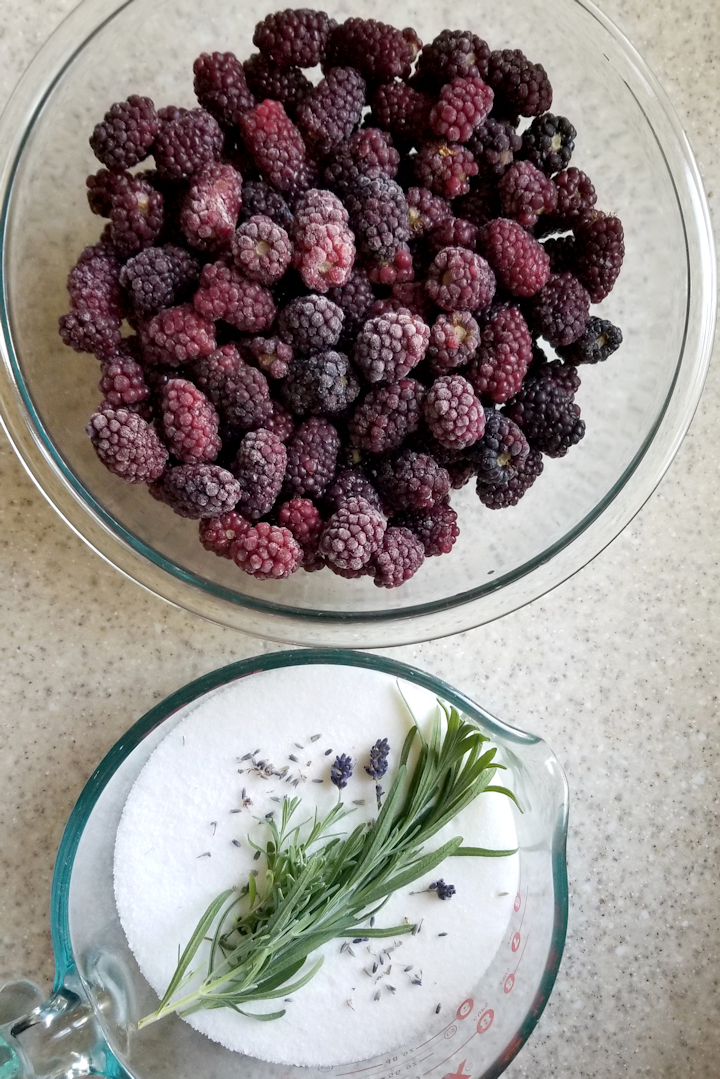 a bowl of blackberries and a bowl of sugar with lavender sprigs