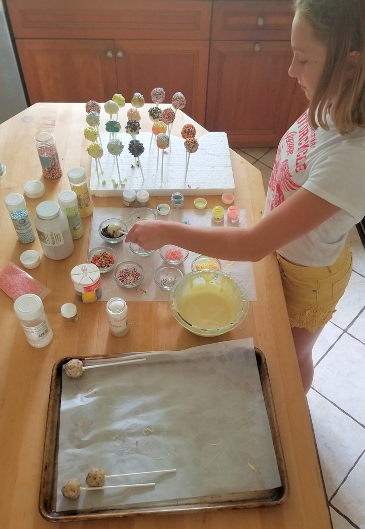 showing the setup for dipping and decorating edible cookie dough pops.