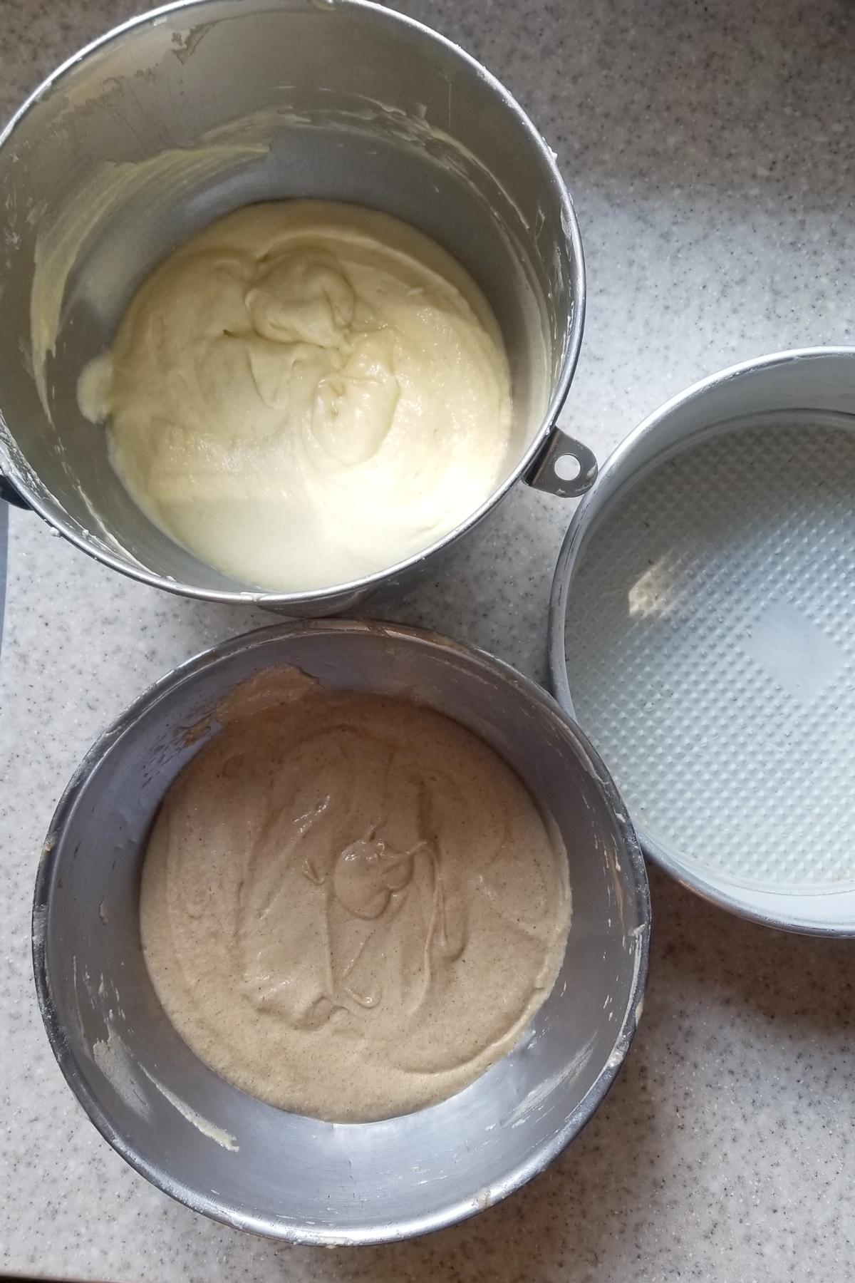 a bowl of white cake batter, a bowl of spiced cake batter and a buttered cake pan